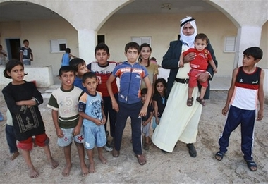 Israeli Bedouin Shahadeh Abu Arar stands with some of his 67 children outside his home in the town of Emek Hefer, Israel , in this photo taken Sunday, Oct. 7, 2007. With eight wives and 67 children,Abu Arrar has given new meaning to the term family man. Arrar, 58, is a member of Israel's impoverished Bedouin Arab community. But even in a traditional society where men commonly have several wives and many children, Abu Arrar is exceptional. (AP Photo/Shaul Golan)
